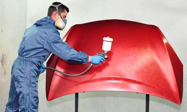 Application de peinture rouge sur métal avec un pistolet pulvérisateur